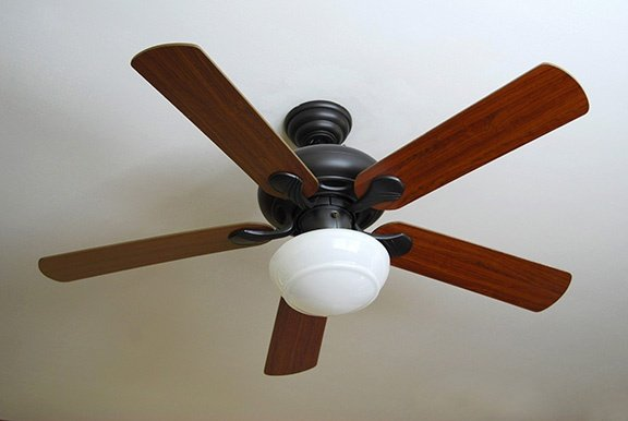 a-modern-ceiling-fan-installed-on-a-textured-white-ceiling_low
