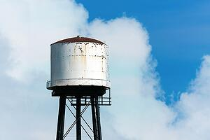 an-old-rusty-water-tower-over-a-partially-cloudy-blue-sky_LOW